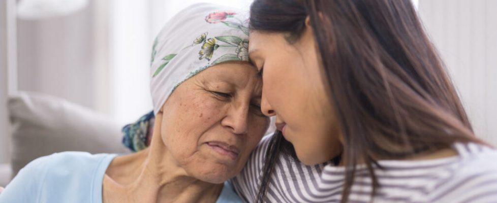 Ethnic elderly woman with cancer embracing her adult daughter